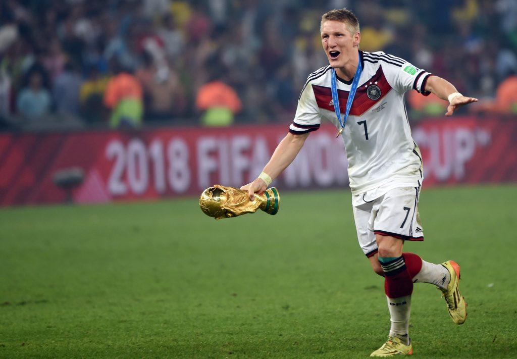 AFP PHOTO   PATRIK STOLLARZ Bastian Schweinsteiger correndo com taça da  Copa do Mundo 78bfe2a220268