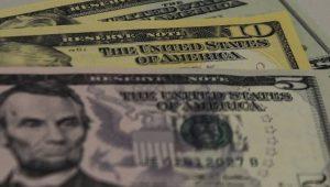 Dólar recua em linha com ajustes no exterior, mas cautela persiste
